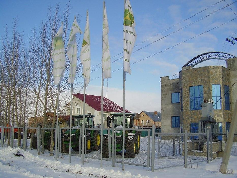 Флаги «John Deere» и «Меркьюри Технолоджи» на флагштоках во дворе магазина «Сельхозтехника»